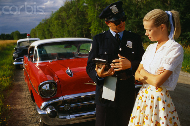 Police Officers Giving Woman Traffic Ticket --- Image by © JDC/LWA/Corbis
